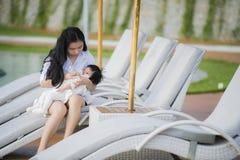 有惯例瓶的年轻愉快和逗人喜爱的亚裔中国妇女护理的女儿女婴在假日热带手段游泳场 免版税库存图片