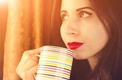 有想法的视域的少妇在手上看对与一杯茶的窗口 免版税库存图片