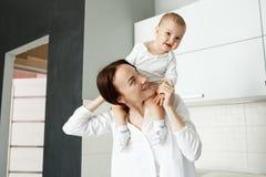 有愉快地微笑大棕色的眼睛的小逗人喜爱的男婴坐母亲脖子和 拿着他的母亲用手 免版税库存图片