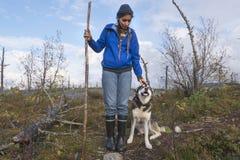 有愉快多壳迁徙的年轻步行的妇女在道路 有她的走在森林里的狗的混合的族种女孩 库存照片