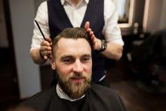 有愉快的人头发被剪在理发师沙龙 图库摄影