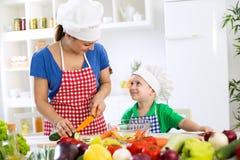 有愉快的可爱的儿子的美丽的母亲食物为晚餐做准备 免版税库存图片
