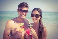 有愉快的夫妇在海滩的鸡尾酒 库存照片