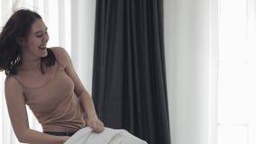 有愉快的女同性恋的夫妇在床上的枕头战,有乐趣和笑 人们,浪漫关系和 股票视频