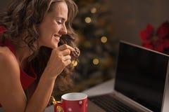 有愉快的妇女圣诞节曲奇饼和usign膝上型计算机 免版税库存照片