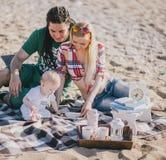 有愉快的家庭在海滩的野餐 库存图片