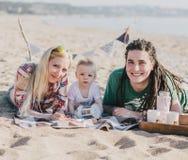 有愉快的家庭在海滩的野餐 免版税图库摄影