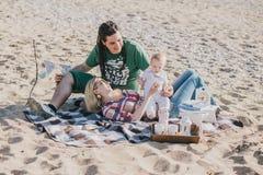 有愉快的家庭在海滩的野餐 免版税库存图片