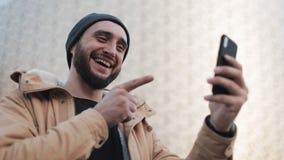 有愉快的年轻胡子的人视频聊天藏品聊天与朋友的智能手机网络摄影 外面 股票录像