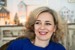 有愉快的微笑的可爱的中年白肤金发的妇女 免版税图库摄影