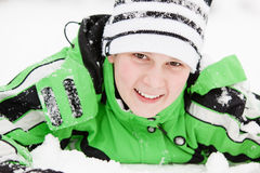有愉快的微笑的逗人喜爱的年轻男孩在冬天雪 免版税库存图片
