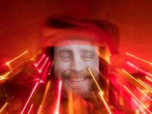 有愉快的有胡子的男性的片剂在屏幕和圣诞老人盖帽上对此与圣诞节属性与线绘与光 图库摄影