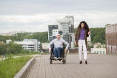 有愉快的残疾人的少妇获得的轮椅的乐趣户外 免版税库存照片