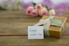 有愉快的母亲节卡片的礼物盒木表面上 图库摄影