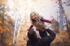 有愉快的父亲的小可爱的女孩在秋天停放得户外 库存图片