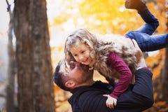 有愉快的父亲的小可爱的女孩在秋天停放得户外 图库摄影