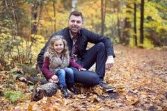 有愉快的父亲的小可爱的女孩在秋天停放得户外 免版税库存图片