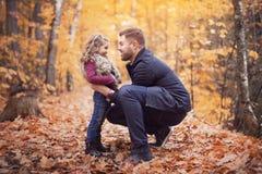 有愉快的父亲的小可爱的女孩在秋天停放得户外 库存照片