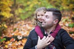 有愉快的父亲的小可爱的女孩在秋天停放得户外 免版税图库摄影