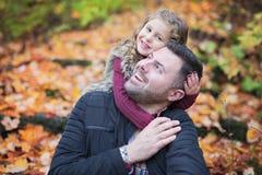 有愉快的父亲的小可爱的女孩在秋天停放得户外 免版税库存照片
