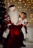 有愉快的矮小的逗人喜爱的孩子的男孩和女孩圣诞老人在圣诞树附近 库存图片