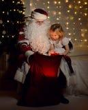 有愉快的矮小的逗人喜爱的孩子的男孩和女孩圣诞老人在圣诞树附近 图库摄影