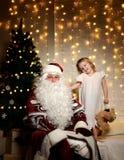 有愉快的矮小的逗人喜爱的孩子的男孩和女孩圣诞老人在圣诞树附近 免版税库存图片