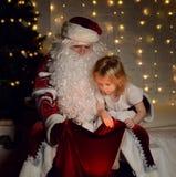 有愉快的矮小的逗人喜爱的孩子的男孩和女孩圣诞老人在圣诞树附近 库存照片