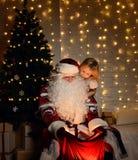 有愉快的矮小的逗人喜爱的孩子的男孩和女孩圣诞老人在圣诞树附近 免版税图库摄影