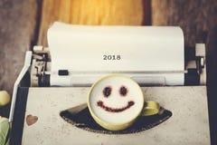 有愉快的面孔咖啡杯的打字机有模糊的消息的2018年, 库存图片