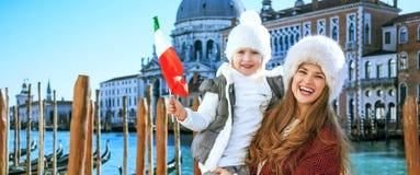 有意大利旗子的母亲和女儿旅行家在威尼斯 免版税库存照片