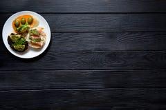 有意大利bruschettas的板材与橄榄色的面团, pesto,火腿,同水准 免版税库存照片