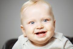 有感兴趣的神色和开朗的笑的婴孩 免版税库存图片