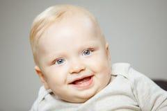 有感兴趣的神色和开朗的笑的婴孩 库存图片