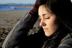 有感觉在海滩的闭合的眼睛的哀伤的妇女痛苦 免版税库存照片