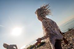 有感觉自由跳跃的上流的白色dreadlocks的妇女在河附近 免版税库存照片