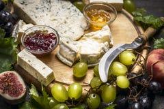 有戈贡佐拉和软制乳酪乳酪刀子的乳酪盘子蜂蜜阻塞清淡和黑暗的葡萄木切板关闭  免版税库存照片