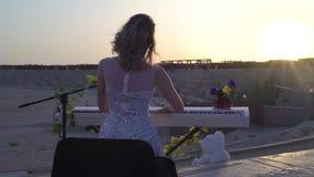 有戏剧浪漫音乐的年轻白肤金发的妇女在日落的数字式钢琴 俏丽的女孩在阶段唱歌执行与太阳  股票视频