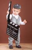 有戏院拍板的逗人喜爱的小男孩 库存照片