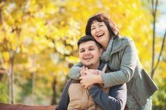 有成人儿子的成熟妇女在秋天公园 免版税库存图片