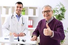 有成功年轻人医生的满意的老患者 库存图片
