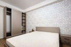 有成对床和床头柜的新的空的棕色卧室 免版税库存图片
