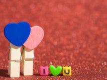有我爱你文本的木心脏夹子从小珠五颜六色在红色地板和背景上 复制文本的空间 情人节, 库存照片
