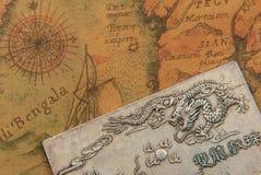 有战斗的龙的古色古香的银盘在古老东方式世界地图 免版税图库摄影