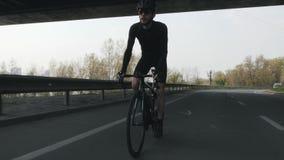 有戴黑成套装备、盔甲和太阳镜的胡子的坚强和适合骑自行车者骑自行车在马鞍外面 前面跟随射击 股票录像