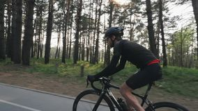 有戴黑成套装备、盔甲和太阳镜的胡子的年轻骑自行车者骑自行车在公园 发光通过树的太阳 Cyclin 股票视频