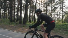 有戴黑成套装备、盔甲和太阳镜的胡子的年轻骑自行车者骑自行车在公园 发光通过树的太阳 Cyclin 股票录像