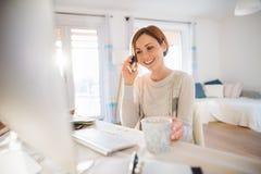 有户内计算机和智能手机的一年轻女人,工作在一个家庭办公室 免版税库存图片