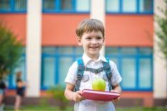 有户外书和绿色苹果的孩子 免版税库存照片