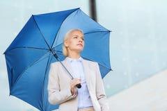 有户外伞的年轻严肃的女实业家 图库摄影